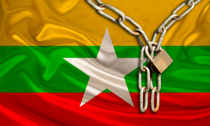 The Myanmar flag with a padlock and chains draped over it.